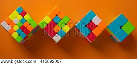 Araras, São Paulo, Brazil, April 4, 2021, Four Magic Cubes With Different Difficulties On Orange Bac