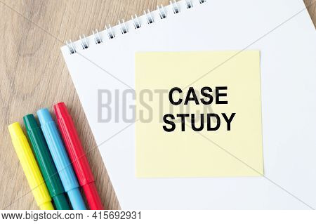 The Text Case Study On Yellow Paper, Which Lies On A White Notebook On A Table Next To Colored Marke
