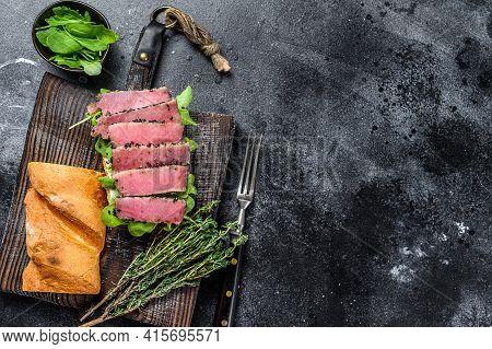 Baguette Tuna Steak Sandwich With Arugula On A Cutting Board. Black Background. Top View. Copy Space