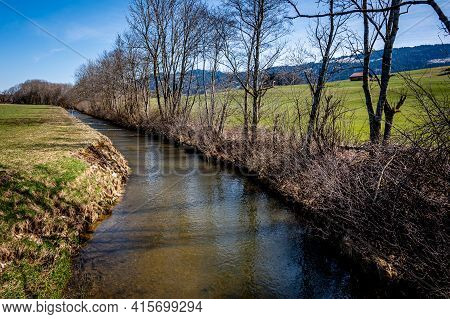 Idyllic Landscape. View Of River, Trees And Agriculture Field In Switzerland. Tranquil Scene.