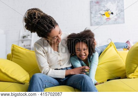 Happy African American Woman Tickling Excited Daughter On Sofa At Home.
