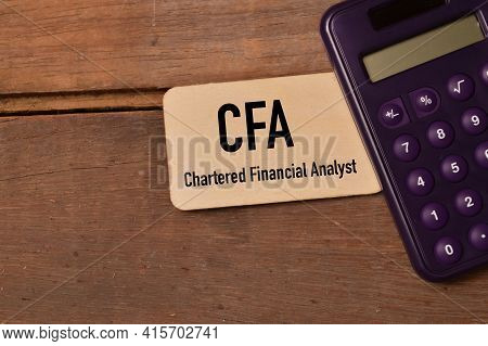 Calculator And Wooden Board Written With Text Cfa Stands For Chartered Financial Analyst