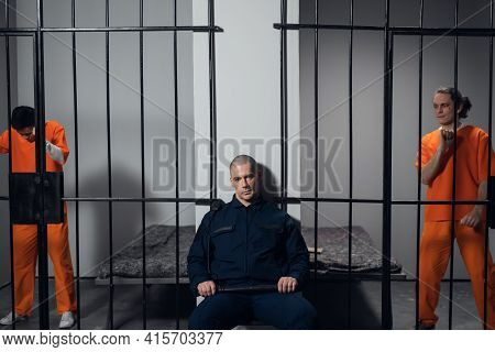 A Strict Prison Guard In Uniform Guards Cells With Prisoners In A Maximum Security Prison.