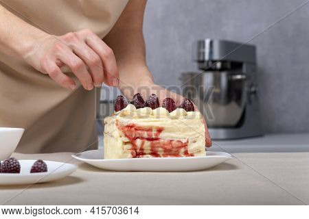 Confectioner Woman Decorates Cake With Raspberries. Vanilla Cream Cake With Berry Filling