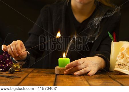 A Fortune Teller Or Oracle With Objects For Fortune-telling Lights A Candle For A Session. Psychic R