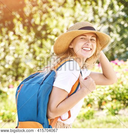 Young Woman With Bright Backpack. Local Tourist. Summer Sunny Day. Green Background. Staycation Week
