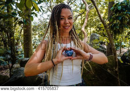 Caucasian Woman With Dreadlocks Smiling And Holding A Blue Stone Heart In Her Hands