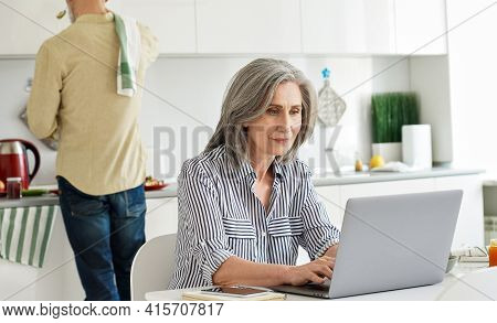 Mature Mid Aged 50s Woman Wife Remote Working Or Distance Learning Online From Home Office Using Lap