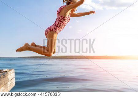 Little Cute Kid Girl In Swimsuit Have Fun Enjoy Pretend Flying Jumping From Pier Dock In Clean Blue