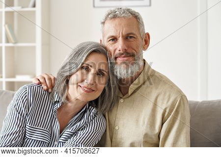 Happy Mature Mid Age Couple Hugging, Enjoying Bonding Sitting On Couch In Apartment. Smiling Affecti