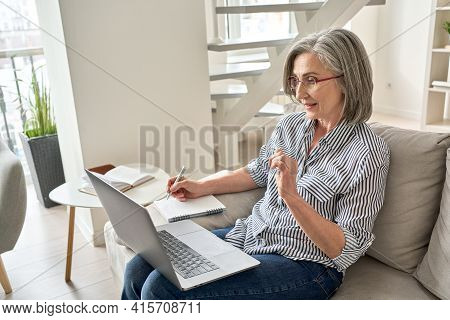 Mature Adult Old Professional Woman Watching Web Training, Online Webinar On Laptop Computer Remote