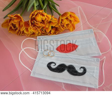 Two Disposable Protective Masks With Painted Mustache And Lips, Two Wedding Rings Next To Bouquet Of