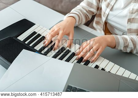 Woman Playing Piano Record Music On Synthesizer Using Notes And Laptop. Female Hands Musician Pianis
