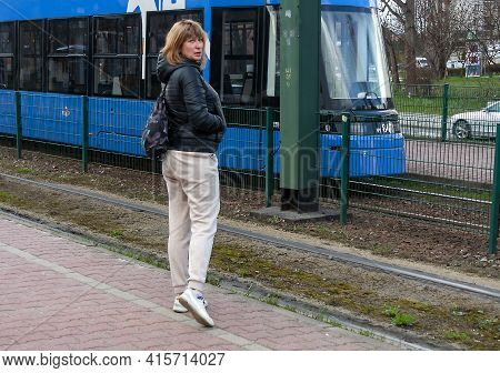 Middle-aged Woman Of A Sports Type In A Jacket And Sweatpants Stands At A Tram Stop Next To A Tram,