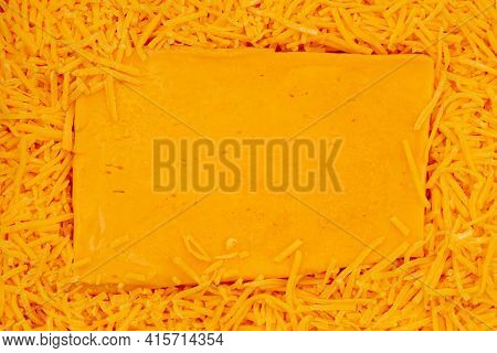Block Of Cheese On Shredded Cheddar Cheese Background With Copy Space For Your Snack Message