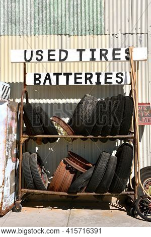 A Rack Of Old Tires, Rims, And  Batteries Are Stored In A Rack Outside Of A Repair Garage
