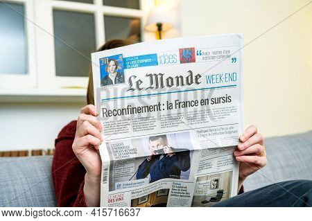 Paris, France - Mar 3, 2021: Woman Reading In Living Room The Latest French Le Monde Newspaper With