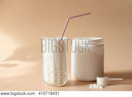 Whey Drink In A High Glass. Whey Protein Vanilla Cocktail. A Jar With Protein Powder And A Scoop Of