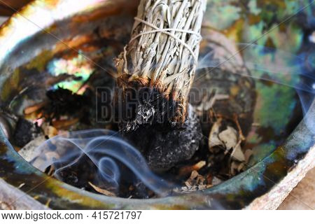 A Close Up Image Of A Burning White Sage Bundle In An Abalone Shell.