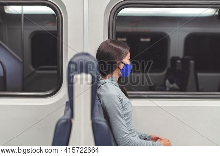 Woman pensive looking out the window during train commute wearing face mask in public transportation. Coronavirus pandemic lifestyle. Passenger commuter using cloth mouth covering.