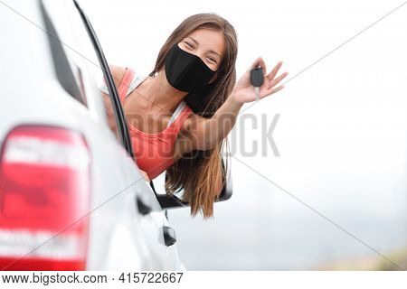 Driving new car happy driver woman wearing face mask for coronavirus showing keys. Drivers license school test success Asian girl car owner.