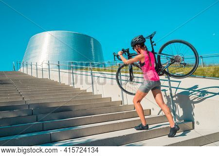 Urban cyclist riding road bike in city carrying bicycle walking up stairs during downtown commute transport travel.