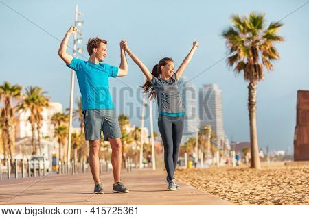 Winning couple training outdoor reaching goal happy of success in fitness. Asian woman and man cheering for weight loss achievement. Runners running on beach.