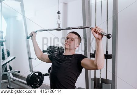 A Man Trains In The Gym On A Simulator, Does Exercises For Different Muscle Groups. Fintes Motivatio