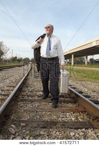 Jobless Senior Businessman Looks Upward, Walking Along Railroad Train Track With Suitcase.