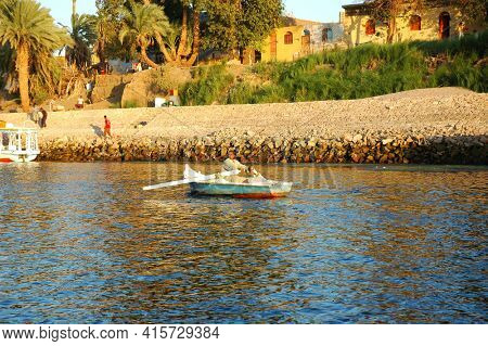 ELEPHANTINE ISLAND, EGYPT - NOVEMBER 2: Local Egyptian rows his boat to Elephantine Island on the Nile River, November 2, 2008. Elephantine is the largest island in the Aswan Region of the Nile.