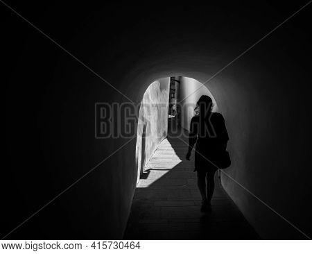 Woman Silhouette Walks Through A Dark Tunnel. Sibiu, Romania, Europe. Black And White Photograph
