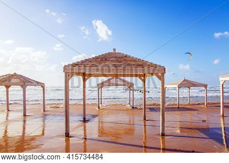Winter sunset on the Mediterranean coast. Beach canopies on the sand are illuminated by sunset.  Israel. Powerful winter surf takes off with snow-white foam