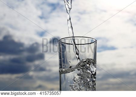 Clean Water Pouring Into Drinking Glass On Background Of Sky With Clouds. Concept Of Health And Fres