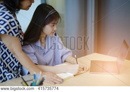 Mother And Daughter Are Teaching And Learning Online Class By Laptop. Adult Woman Teaches Child The
