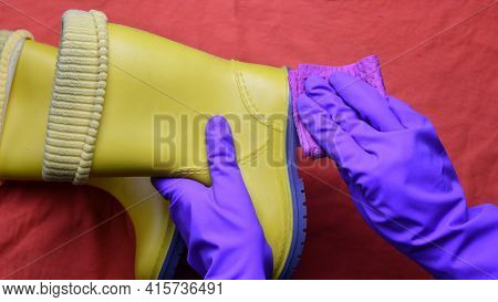 Hands In Purple Rubber Gloves Clean And Wipe Dirty Sole Of Kids Yellow Boots With Wet Rag. Pov Pair