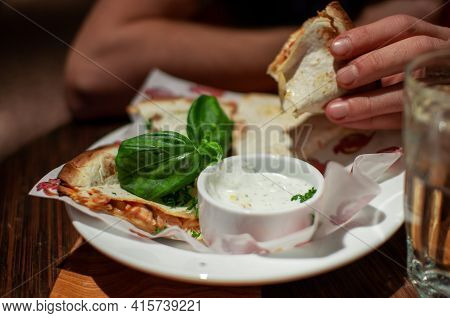 Man Eating Fresh Delicious Quesadilla In Restaurant