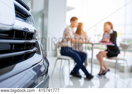 Selective Focus On A New Car And Blur The Dealership Professional Salesman Negotiate And Present. Co