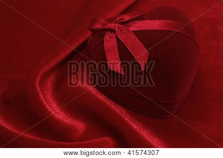 Red Heart Shaped Gift Box On The Red Velvet