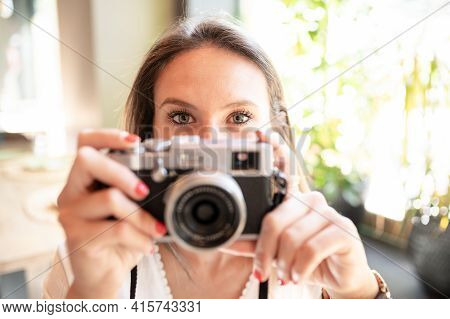 Young Girl With Pretty Eyes Holding A Vintage Camera In Her Hands
