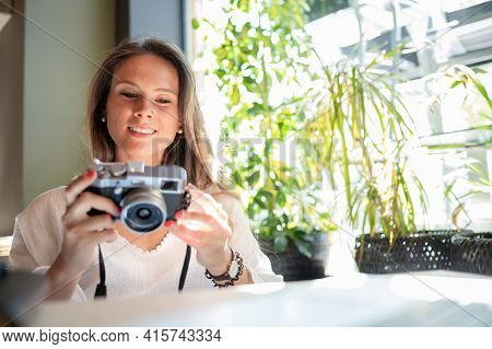 Beautiful Young Woman Watching Photos On Her Vintage Camera.traveler Concept