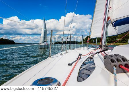 Sailboat Sailing On A Lake. Mainsail Stretched In Wind, With Bright Sun In Background. Sail Over Blu