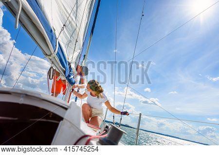 Young Woman And Man Sailing On A Yacht. Sailboat Crewmember Trimming Main Sail During Sail On Vacati
