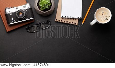 Office desk with supplies, photo camera and coffee over black leather table. Top view flat lay with copy space