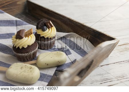 White Cookie Ice Creams On A Stick And Tasty Muffins And Cupcakes On A Tray On A Wooden Background.