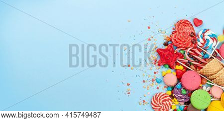 Various sweets assortment. Candy, bonbon and macaroons on blue background. Top view flat lay with copy space
