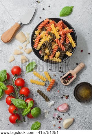 Fresh Raw Tricolore Fusilli Pasta In Black Bowl With Cherry Tomatoes And Basil, Garlic And Oil With