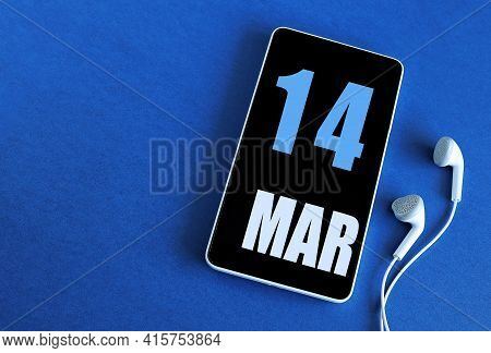 March 14. 14 St Day Of The Month, Calendar Date. Smartphone And White Headphones On A Blue Backgroun