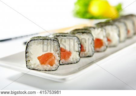 Philadelphia Sushi Roll made with Smoked Salmon. Maki sushi with nori seaweed outside, salmon and cream cheese inside. White plate with wooden chopsticks on white table