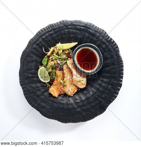 Teppanyaki Style Salmon - Grilled Salmon Fillet with Soy Sauce and Vegetables. Japanese Teppanyaki Salmon Steak garnished with lemon and green bean leaf. Black asian plate on white background top view