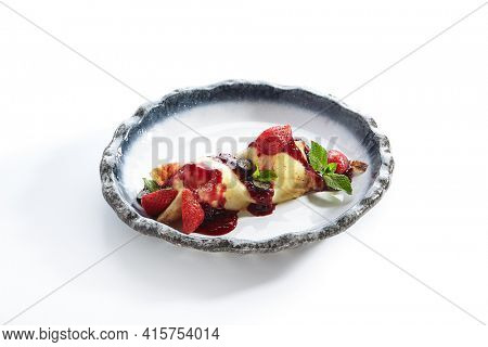 French Style Crepes - Cream Crepes with Berry and Fruit. Pancake Breakfast on white and blue plate isolated on white background. Mixed berry crepes garnished with mint and sweet sauce